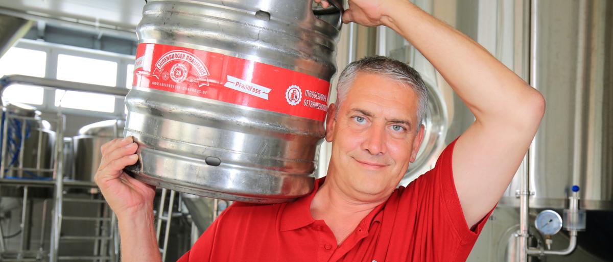 Unternehmer Ulf Steinforth trägt ein Bierfass auf der Schulter